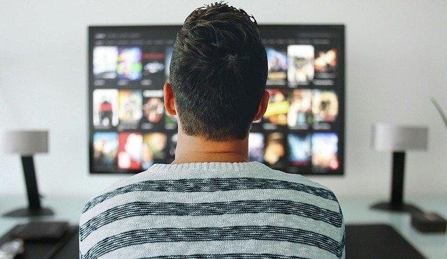 man sitting watching tv